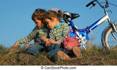 Boy and girl sitting on the grass playing their games