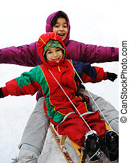Boy and girl sledging on snow, happiness for brother and sister