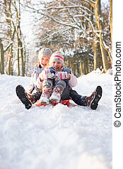 Boy And Girl Sledging Through Snowy Woodland