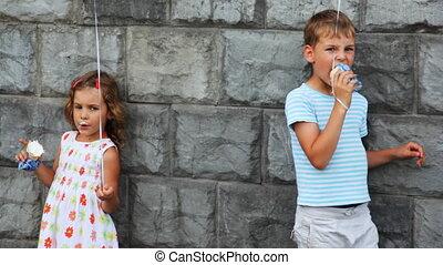 boy and girl standing, eat ice cream