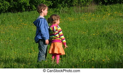 boy and girl stands in meadow