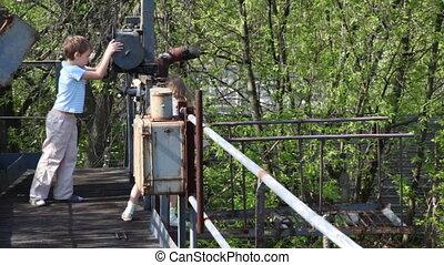 Boy and girl study mechanism winch on old abandoned bridge
