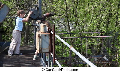 Boy and girl study mechanism winch on old abandoned bridge