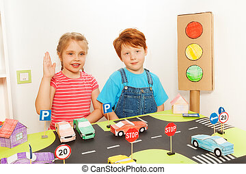 Boy and girl studying road traffic regulations - Two happy...