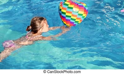 boy and girl swim in pool with inflatable multi-colored toys