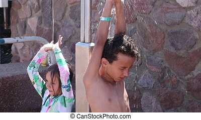 boy and girl take an outdoor shower after swimming in the sea