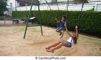 boy and girl teenager swinging on a swing with bare feet on...