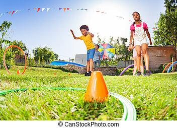 Boy and girl throw hula hoops rings totarget