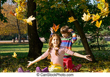 Boy and girl throw yellow leaves up in autumn