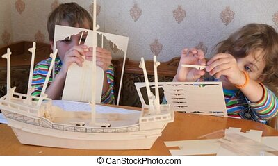 boy and girl together constructing toy model of ship