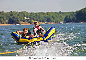 Two kids having fun bouncing on a tube behind a boat.