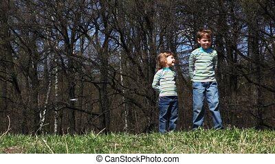 boy and girl turns, jumps and run across field in spring