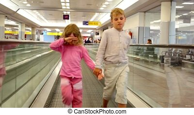 Boy and girl walk together by travelator in the airport