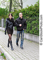 Boy and girl walking down the street arm in arm