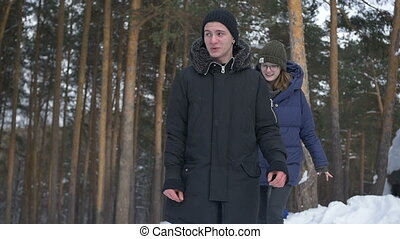 Boy and girl walking in the park in winter