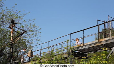 Boy and girl walking on abandoned bridge for maintenance of wagons