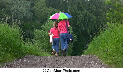 boy and girl walks on way from camera in park under umbrella