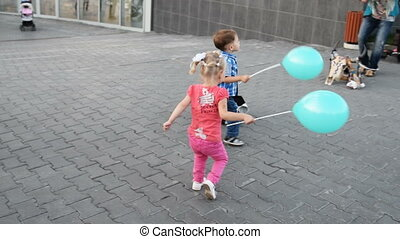 Boy and girl with balloons playing in the street