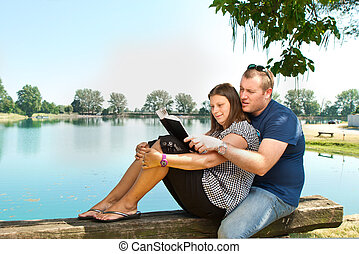 boy and girl with books on the nature near lake