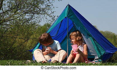 Boy and girl with glass sit in tent, he opens bottle of water