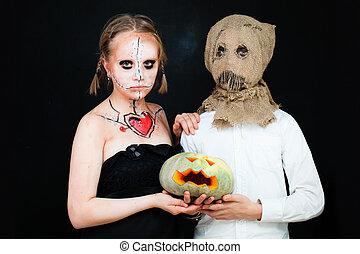Boy and Girl with Halloween Makeup holding Pumpkin