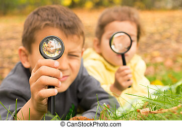 boy and girl look through a magnifying glass on the background of green grass and yellow leaves