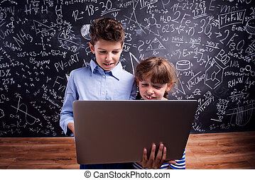 Boy and girl  with notebook against big blackboard, school