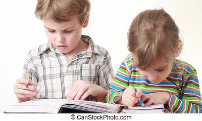 boy and girl with pencils writing on notebook on white...