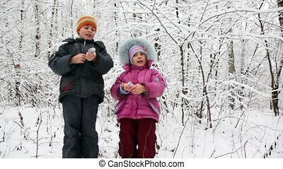 boy and girl with petards in hands in snow forest