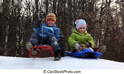 boy and girl with sleds ride down snow mountain