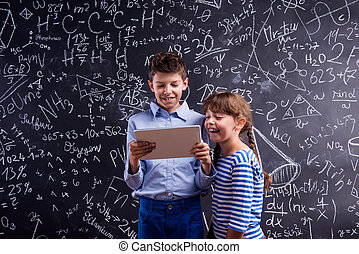 Boy and girl  with tablet against big blackboard, school