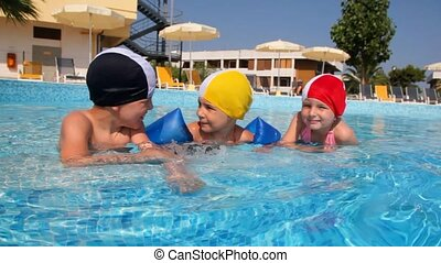 Boy and girls in swimming caps are talking in the pool - Boy...