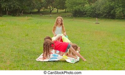 Boy and girls play twister in the park on the grass near the trees. Slow motion