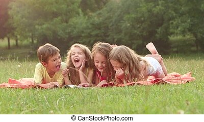 Boy and girls read a book laughing in the garden lying on...