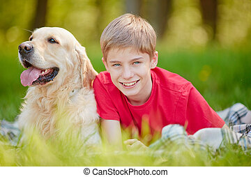 Boy and his dog - Happy boy with his pet relaxing in grass...