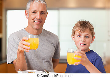 Boy and his father having breakfast