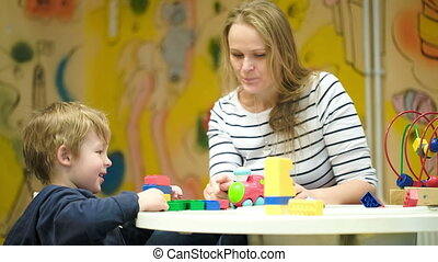 Boy and his mom playing with building kit and toy steam train