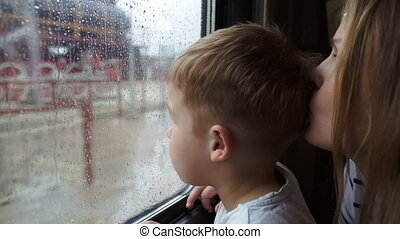 Boy and his mother looking out the window of train while it's rainy