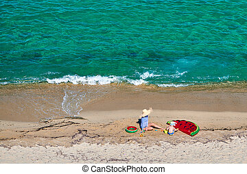Boy and his mother on beach with inflatable float