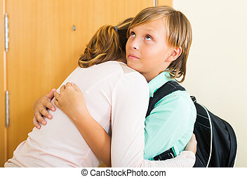 Boy and his mother staying near flat entrance and hugging