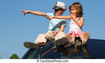 Boy and his sister sit on roof of car - boy in captain's cap...