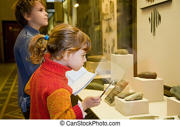 boy and little girl at excursion in historical museum near exhibits of ancient relics in glass cases