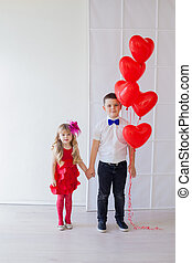 Boy and little girl brother and sister with balloons