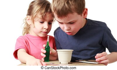 boy and little girl corrects seed plants in pot with soil