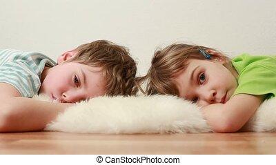 boy and little girl lie on floor on shaggy carpet - Little...