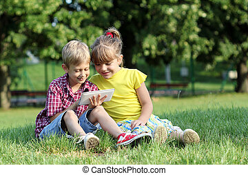 boy and little girl play with tablet pc in park