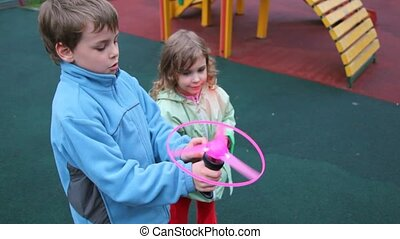 boy and little girl plays with hand gear propeller