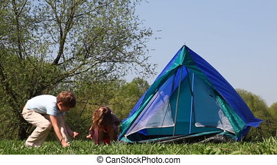 Boy and little girl pull cords of tent in woods