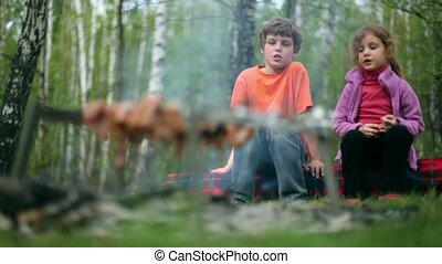 Boy and little girl sit and talk, meat cooking on embers