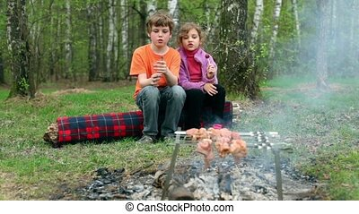 Boy and little girl sit on log, bot hold empty glass and girl eat candy